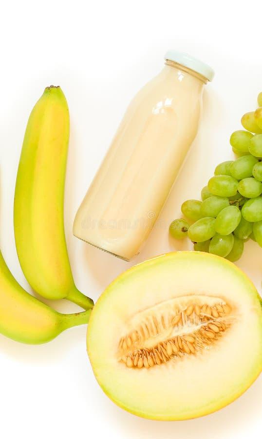 Butelka melon, winogrona, bananowy sok i składniki odizolowywający na bielu, zdjęcia stock