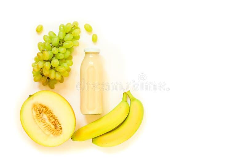 Butelka melon, winogrona, bananowy sok odizolowywający na bielu zdjęcia stock