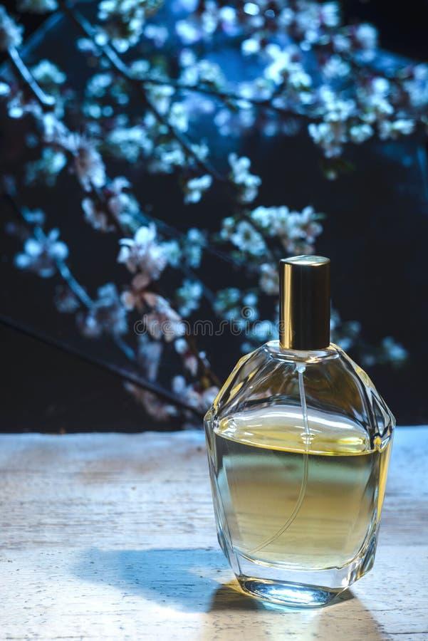 Butelka men's pachnidło na ciemnym kwiecistym tle obrazy stock