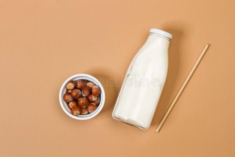Butelka mleka z orzechami laskowymi w białej miseczce na brązowym tle obraz royalty free