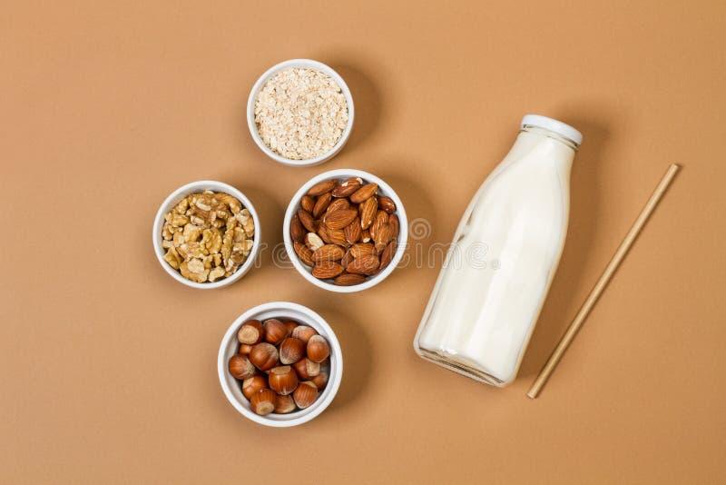 Butelka mleka z orzechami w białych miseczkach na brązowym tle zdjęcia stock