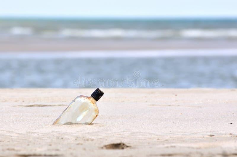 Butelka na piasek plaży zdjęcia stock