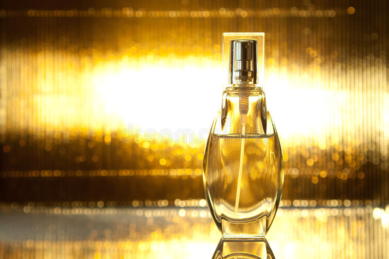 Butelka pachnidło na złocistym tle obraz stock