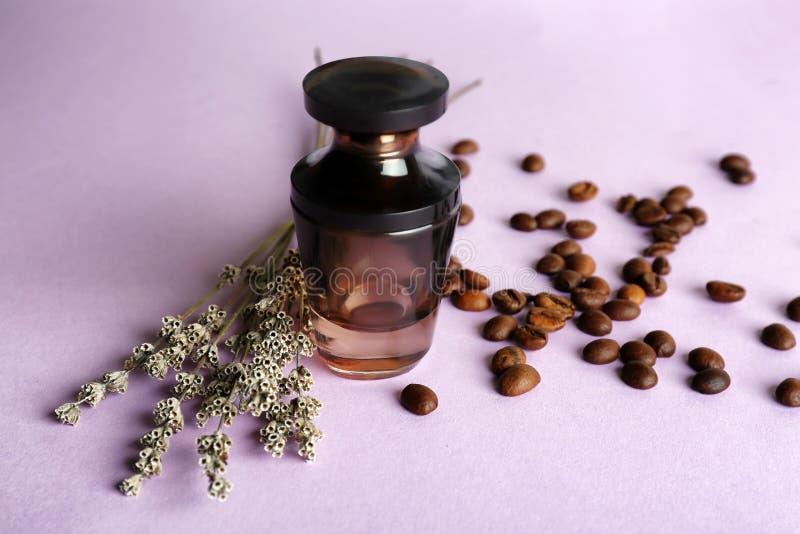 Butelka pachnidło z kwiatami i kawowymi fasolami na koloru stole zdjęcia stock