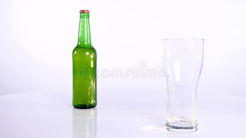 Butelka piwo nalewa w filiżankę na białym tle obrazy stock