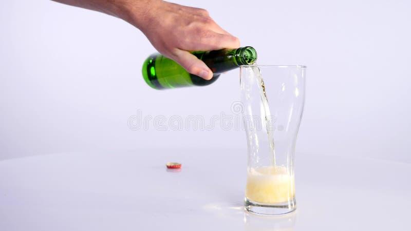 Butelka piwo nalewa w filiżankę na białym tle fotografia royalty free