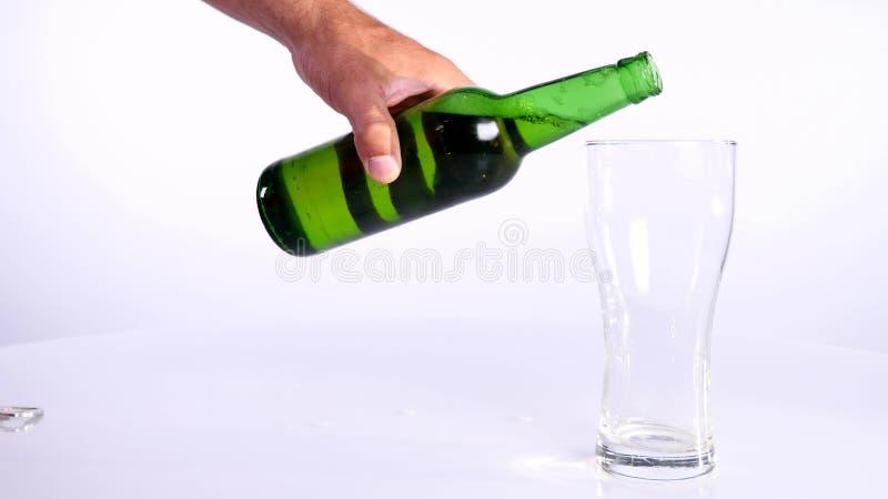 Butelka piwo nalewa w filiżankę na białym tle fotografia stock