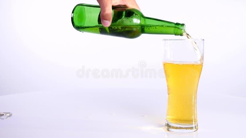 Butelka piwo nalewa w filiżankę na białym tle obraz stock