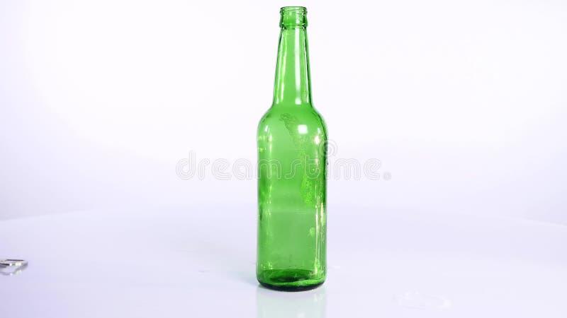 Butelka piwo nalewa w filiżankę na białym tle zdjęcie stock
