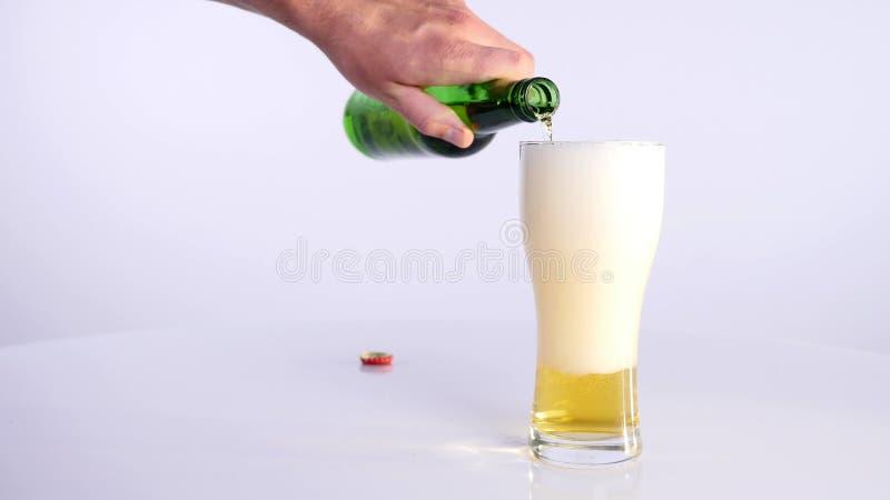 Butelka piwo nalewa w filiżankę na białym tle zdjęcia stock