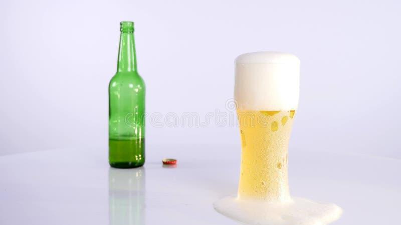Butelka piwo nalewa w filiżankę na białym tle zdjęcia royalty free