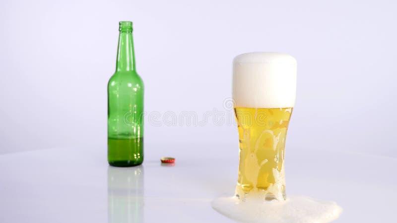 Butelka piwo nalewa w filiżankę na białym tle zdjęcie royalty free