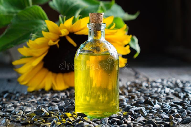 Butelka słonecznikowy olej, ziarna i żółty słonecznik, zdjęcia stock