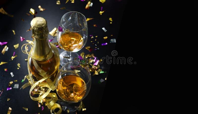 Butelka szampan i dwa szkła wino odizolowywających na czarnym tle, zdjęcia stock