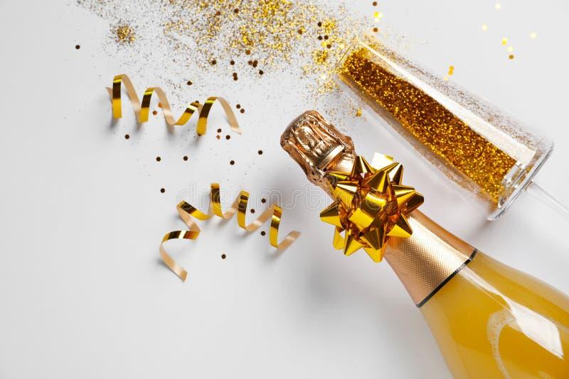 Butelka szampan i szkło z złocistą błyskotliwością na białym tle, odgórny widok komicznie zdjęcie royalty free