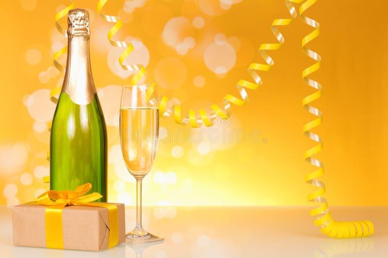 Butelka szampan, szkło wino, prezent w pudełku i serpentyna, na żółtym tle obraz royalty free