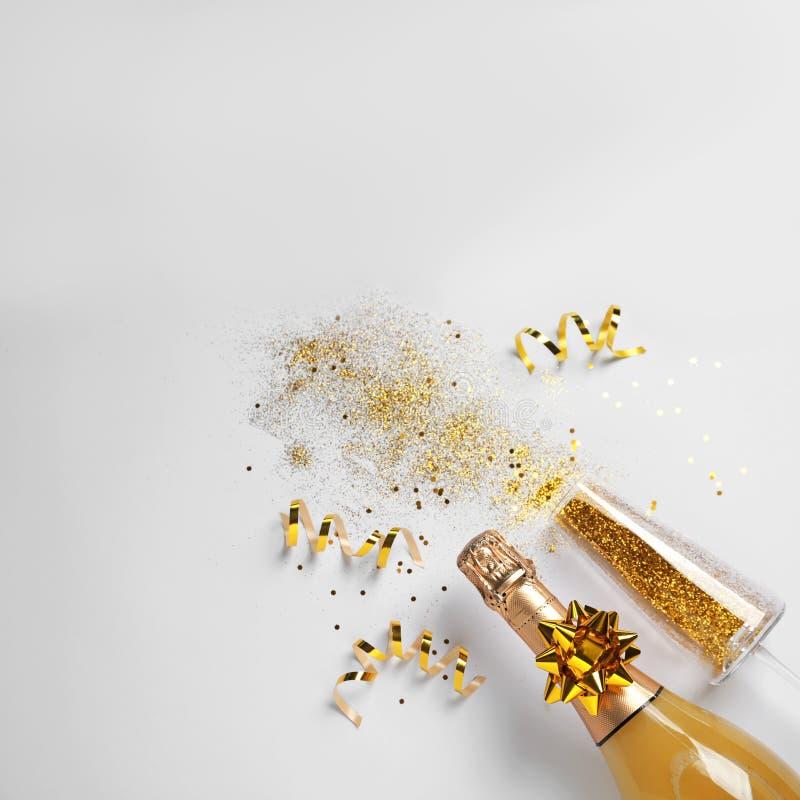 Butelka szampan, szkło z złocistą błyskotliwością i przestrzeń dla teksta na białym tle, Komicznie świętowanie zdjęcia royalty free