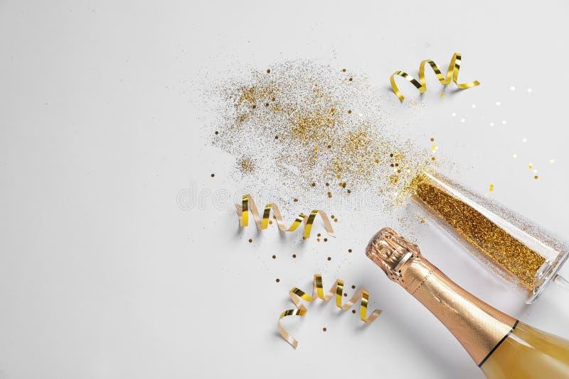 Butelka szampan, szkło z złocistą błyskotliwością i przestrzeń dla teksta na białym tle, Komicznie świętowanie fotografia royalty free