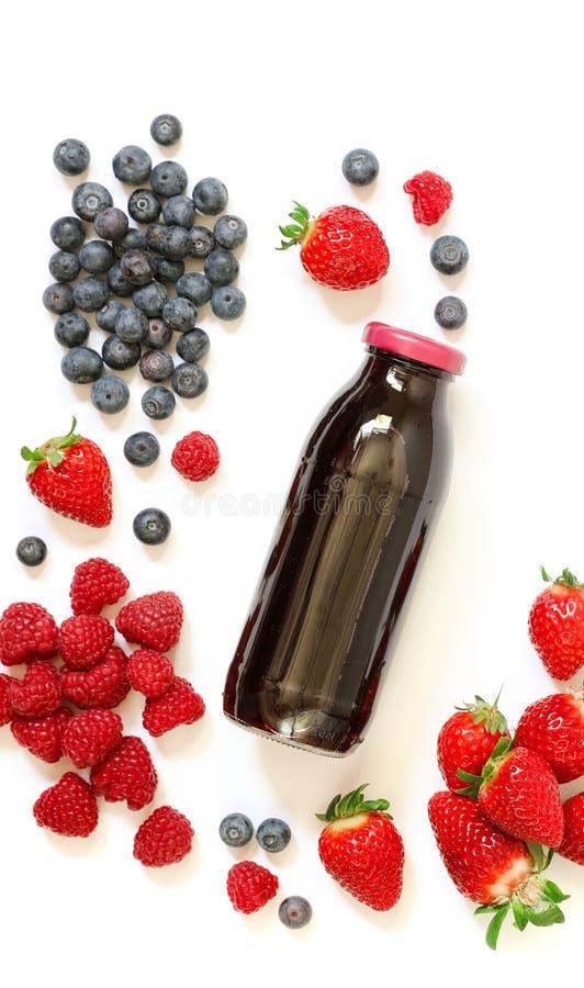 Butelka truskawki, malinki, czarna jagoda sok odizolowywający na bielu zdjęcia stock