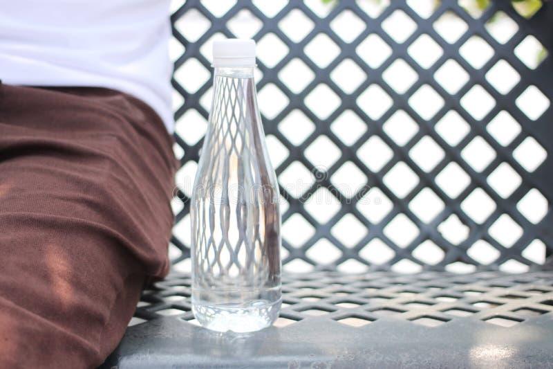 Butelka umieszczająca na stalowym krześle obok mężczyzny jest ubranym tro woda fotografia stock