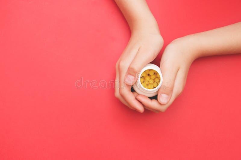 Butelka w żeńskiej ręce z żółtymi pigułkami na czerwonym tle, selekcyjna ostrość Pojęcie dla zapobiegania zimna, antidepressants, obrazy royalty free