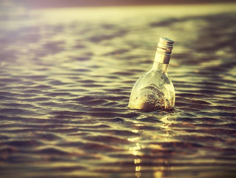 Butelka w wodzie przy zmierzchem, retro instagram rocznika skutek obrazy stock