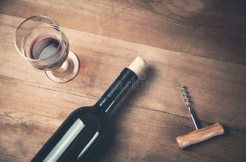Butelka wina szkło na drewnianym tle i corkscrew zdjęcie stock