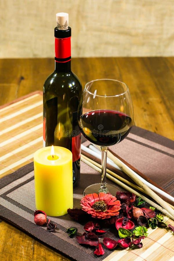 Butelka wino i, dekorujący kwiaty i liście na stole obrazy royalty free