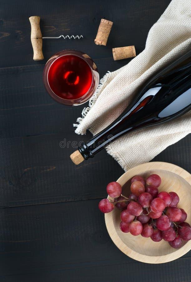 Butelka wino, wina szkło, winogrona i corkscrew na zmroku stole, fotografia stock