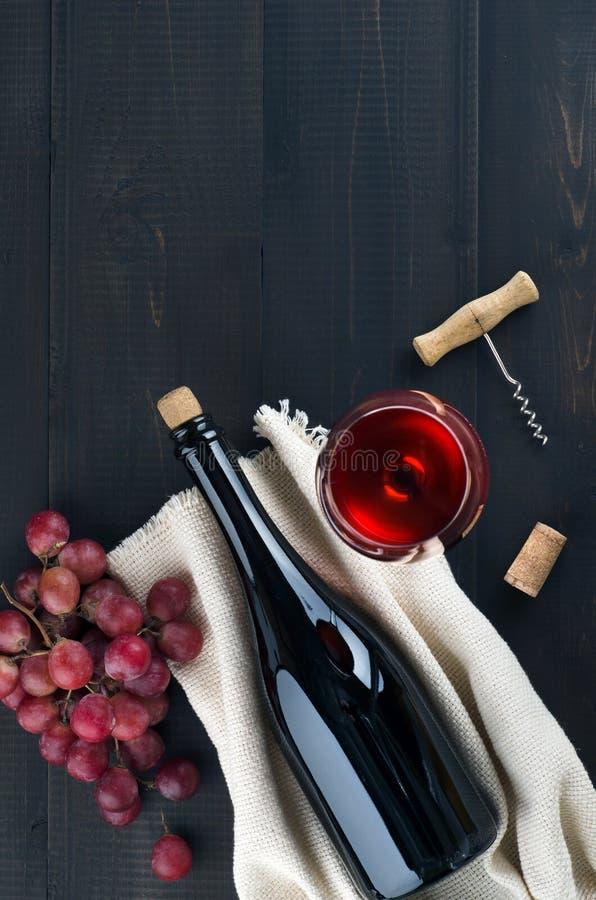 Butelka wino, wina szk?o, winogrona i corkscrew na ciemnym tle, zdjęcia stock
