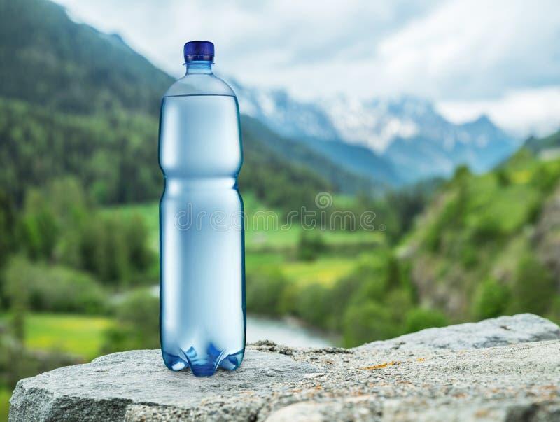 Butelka woda na kamieniu Zamazani śnieżni góra wierzchołki i gr zdjęcie stock