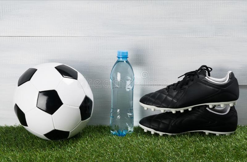 Butelka woda na zielonym gazonie obok butów dla futbolu i piłki obrazy stock