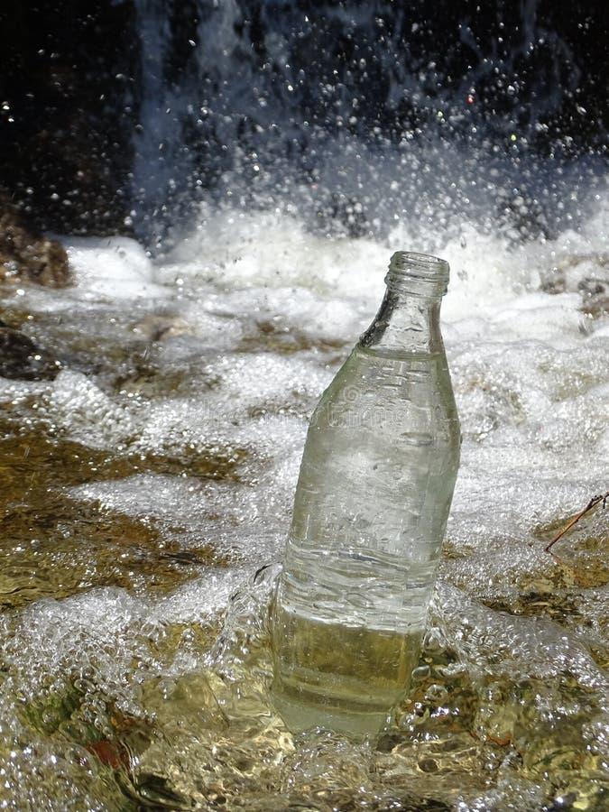 Butelka woda w strumieniu blisko siklawy fotografia stock