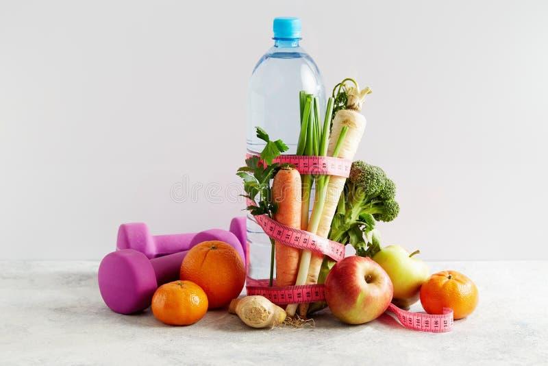 Butelka woda z różową pomiarową taśmą, warzywami i owoc, obraz royalty free