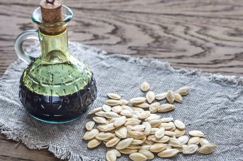 Butelka z bania olejem na drewnianym tle zdjęcia royalty free