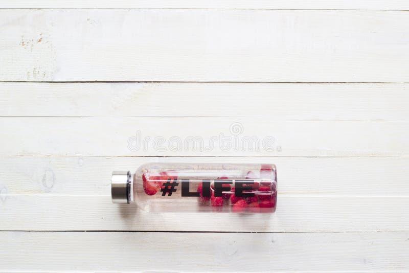 Butelka z odświeżenie napojem, woda z truskawkowymi plasterkami z hashtag życiem na białym drewnianym tle, obraz royalty free