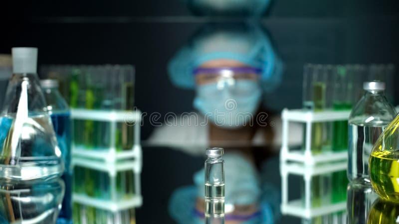 Butelka z przejrzystym cieczem na stole przed lab pracownikiem, badania obrazy stock