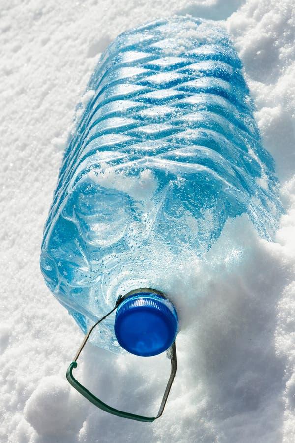 Butelka zimna woda w śniegu obraz stock