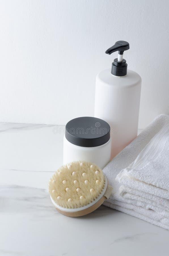 Butelki balsam dla włosy, szamponu i stosu biali ręczniki na bielu, wykładają marmurem półkę Vertical strzał zdjęcie stock