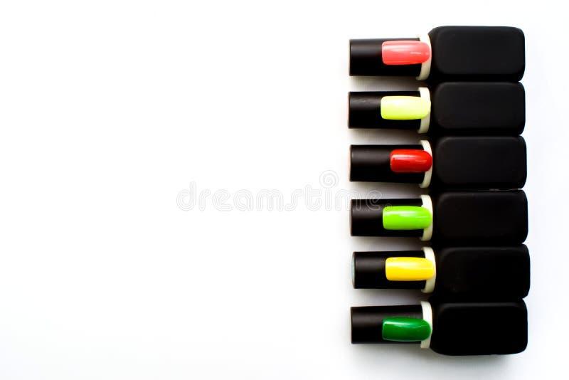 Butelki gwoździa połysk na kolorowym drewnianym stole zdjęcia royalty free