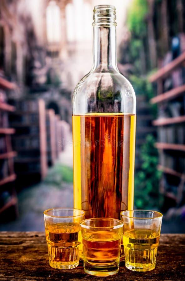 Butelki i szkła strzały z żółtym liqour zdjęcia royalty free
