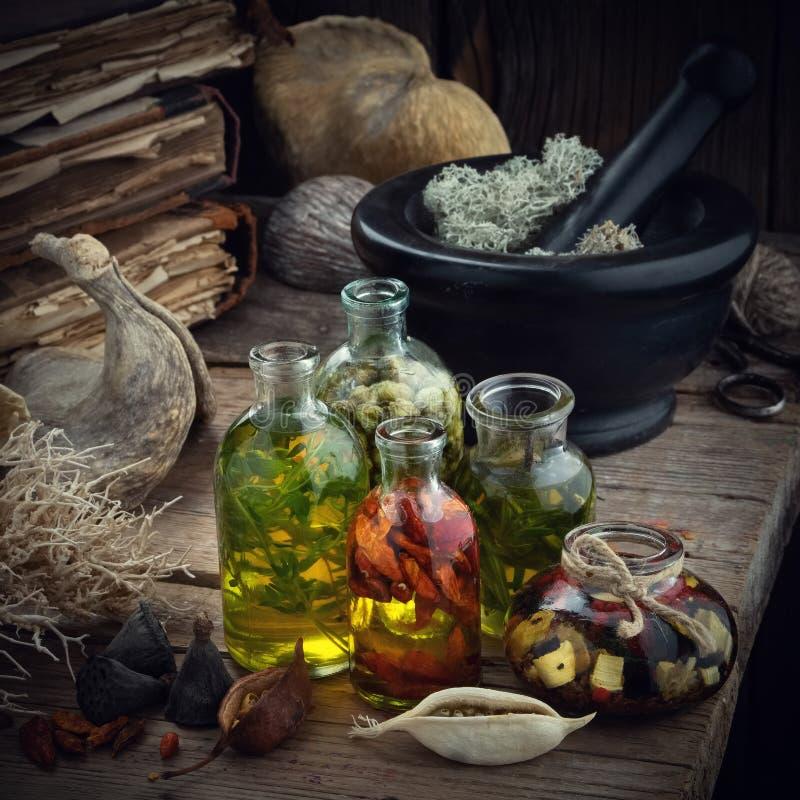Butelki istotny olej lub napój miłosny, moździerz wysuszony mech, stare książki, suszą korzenie i rośliny na starym drewnianym st zdjęcie royalty free