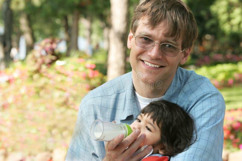 butelki ojca dziecka żywienia park obraz stock