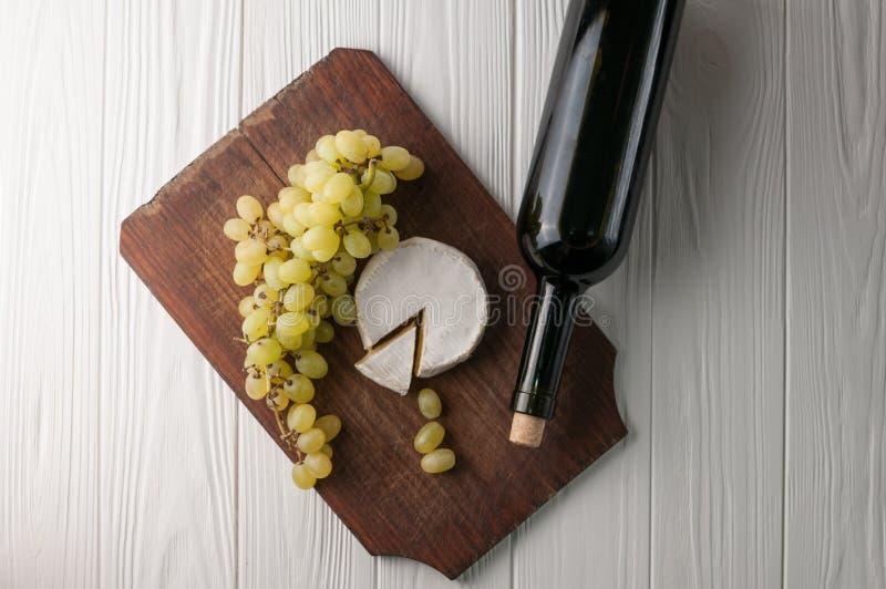 Butelki wino na białym drewnianym tle z winogronami i Camembert serem obrazy stock