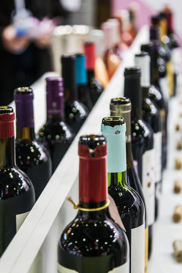 Butelki wino na odpierającym sklepie lub degustaci obrazy royalty free