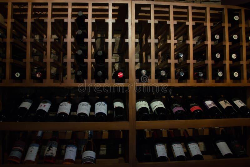 Butelki wino w lochu, restauracja, elita piją na półkach z pisać imionami zdjęcie stock