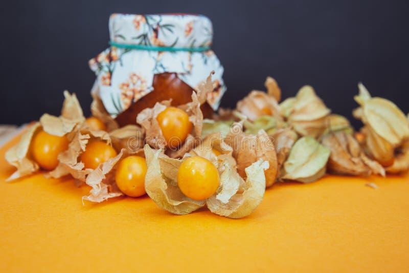 Butelki z pęcherzyca dżemem i świeżą owoc na pomarańcze obraz stock