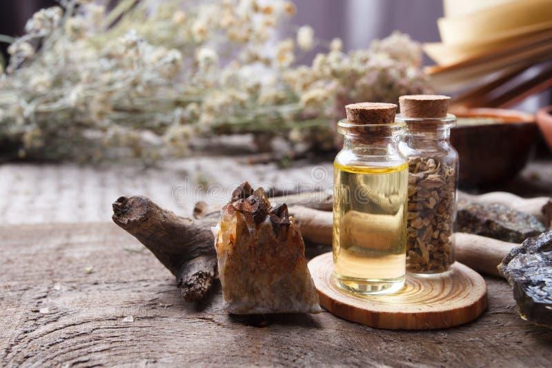 Butelki z ziele, suchymi kwiatami, kamieniami i magia przedmiotami na czarownica drewnianym stole, Occult, ezoteryczny, wróżba i  zdjęcia stock