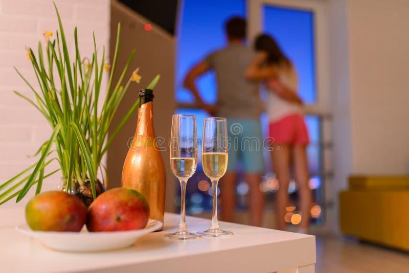 Butelkuje i dwa szkła szampan na stolik do kawy w żywym pokoju, parze w miłości obejmującej przy tłem i patrzeć, zdjęcia royalty free