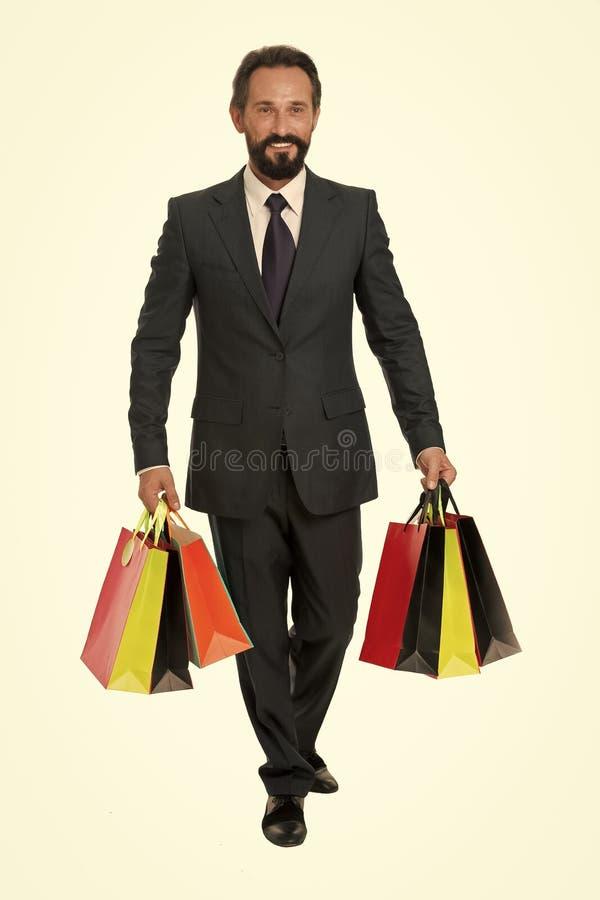 Butik galerii klient M??czyzna dojrza?y kupuj?cy niesie torba na zakupy bielu t?o Pomy?lny biznesmen wybiera tylko obraz royalty free